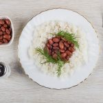 Red beans with boiled rice in plate, salt, bowl with beans, fork on wooden table. Top view