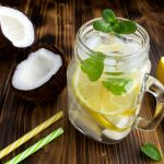 Cold lemonade with coconut,lemon and mint on the brown wooden background
