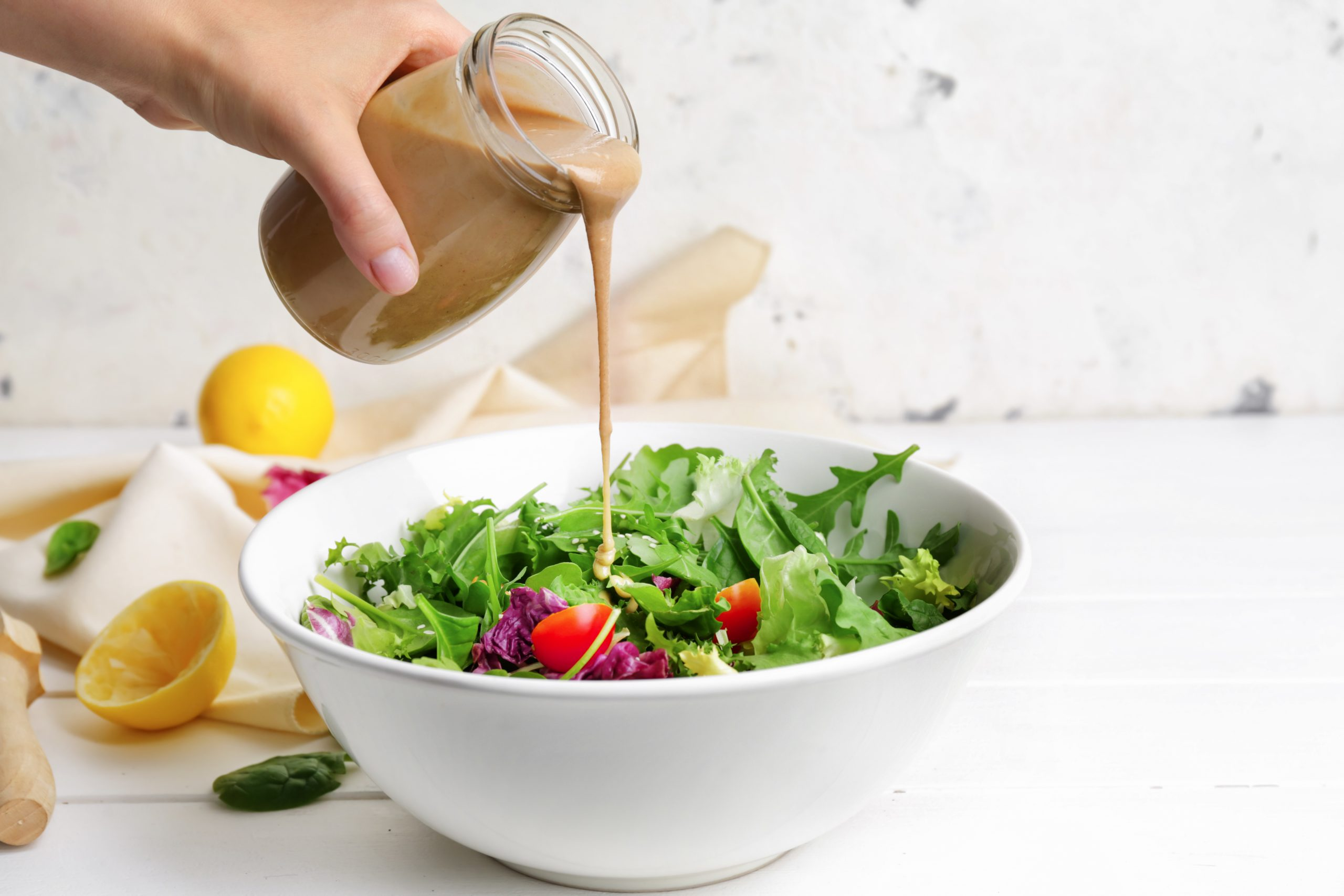 Woman pouring tasty tahini from jar onto vegetable salad in bowl