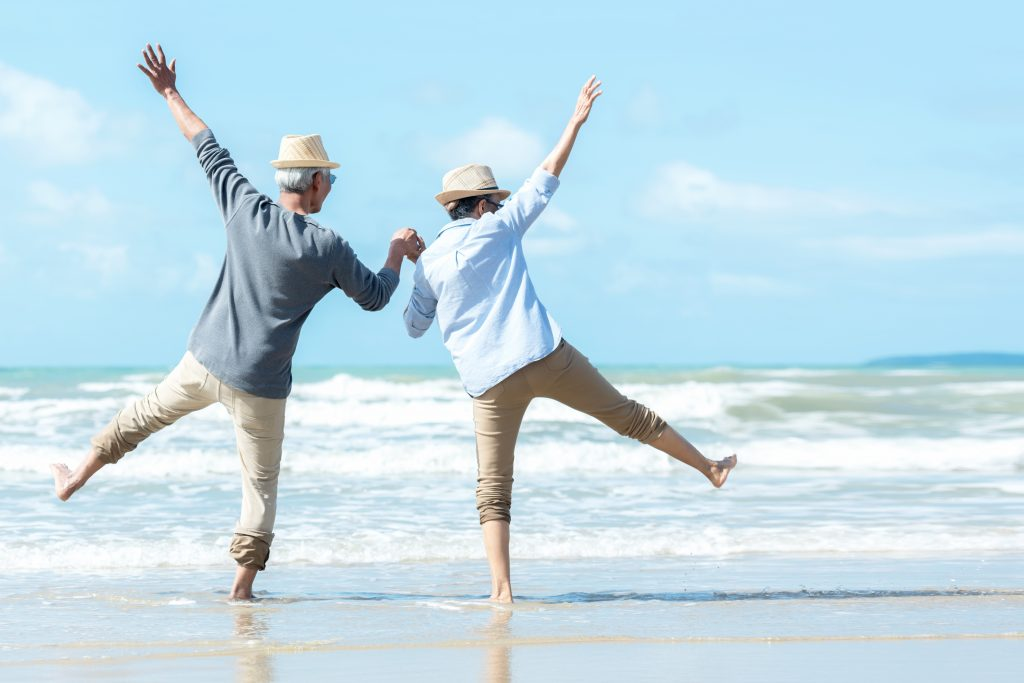 Healthy Lifestyle senior couple jumping on the beach happy in love romantic and relax time. Tourism elderly family travel leisure and activity after retirement in vacations and summer.